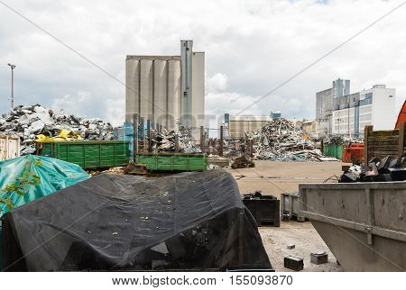 Waste solution dump pile in the yard of a factory with big furnace and processing unit in the background with large clouds and steam from pipes above