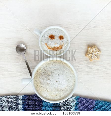 small and large cup of frothy cappuccino standing together in a cheerful snowman top view / good mood for winter coffee break