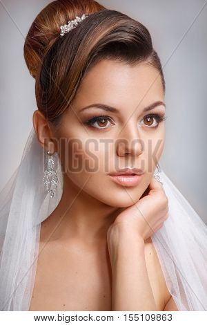 Beautiful bride with fashion wedding hairstyle - on white background. Closeup portrait of young gorgeous bride  in satin gloves. Wedding. Studio shot.Beautiful bride portrait with veil