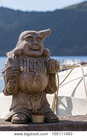 Hakone Japan - September 27 2016: A wooden statue of the laughing and obese Japanese God Ebisu stands at the shoreline of Lake Ashi. White color and rope of boat forest and water.