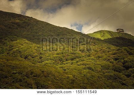 Hakone Japan - September 27 2016: The cable car terminus near the top of Mount Komagatake sits alone near the flank and surrounded by forests. Sun lightens some forest patches brighter than others. Dark rain clouds.