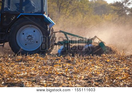 The sloping field. Big blue tractor plow plow the land after harvesting the maize crop on a sunny clear autumn day.