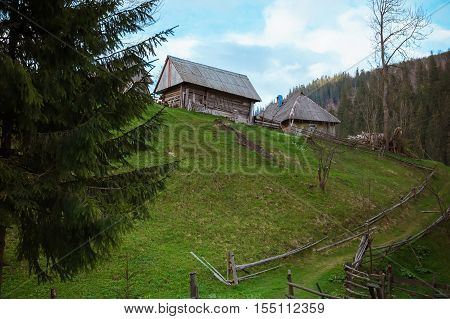 Spring in the mountains. Old dilapidated wooden houses on the green grass in the mountain village on a background of blue sky with clouds