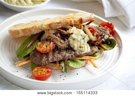 Steak sandwich with salad, grilled onions and aioli.