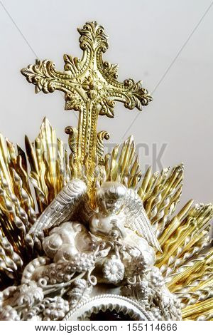 Vertical photo in color about a close up of a monstrance made of metal, focused in the cross with shallow Depth of field