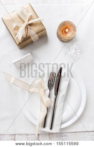 Beautifully elegant decorated table for holiday - wedding or valentine day with modern cutlery bow glass candle and gift top view