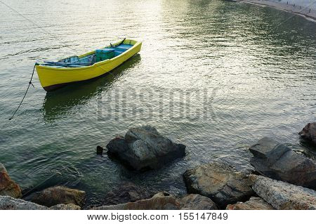 lonely yellow boat rocking on the waves in the sea