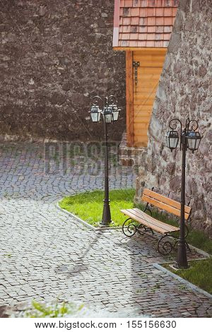 Bench for rest on the territory of the ancient castle with stone walls. Beautiful resting place
