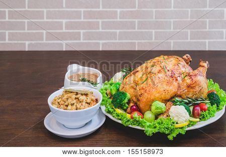 Roasted turkey stuffing garnished with Vegetables served with gravy sauce on a rustic style table. Christmas Dinner