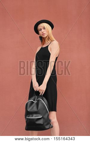 Stylish young woman in black dress with leather rucksack on brown background