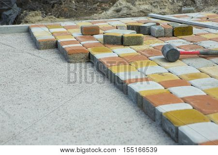 Laying Paving Slabs by mosaic close-up. Road Paving construction. Repairing sidewalk. Workers laying stone paving slab. Laying colored tiles in a city park (garden). Fixed tessellated sidewalk tile