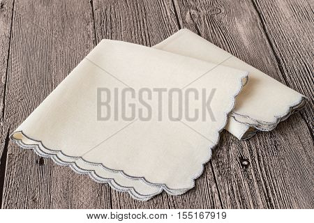 Two handkerchiefs with shaped edge on gray wooden background.