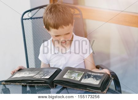 Little 7 Years Old Boy Browsing Old Photo Album.