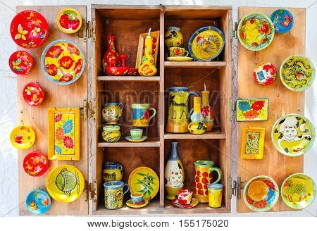 Rethymnon Island Crete Greece - July 1 2016: The wooden shelf of Greek souvenir store with Greek hand-made souvenirs - colorful ceramic cups and plates with pictures of cats animals and flowers.