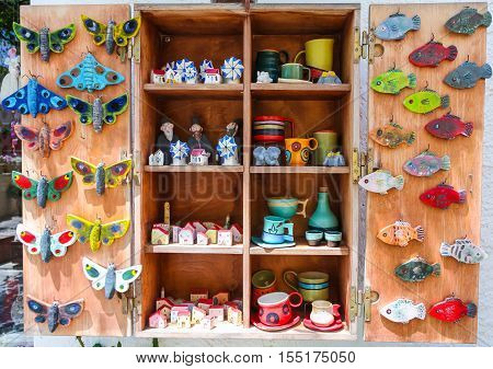 Rethymnon Island Crete Greece - July 1 2016: The wooden shelf of Greek souvenir store with Greek hand-made souvenirs - butterfly fish toys colorful cups and plates Greek monk windmill and small houses