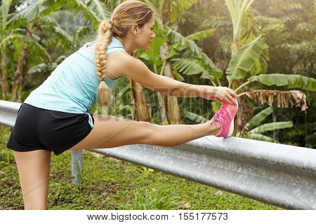 Caucasian Sportswoman With Braid Stretching And Warming Up Her Legs, Preparing Her Muscles Before Go