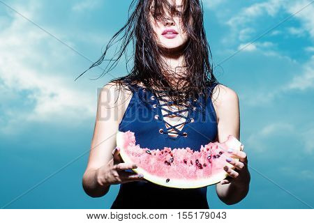 Young pretty woman or girl with cute sexy face and wet long brunette hair in blue swimsuit posing with slim fit body eating red watermelon outdoor on sky background