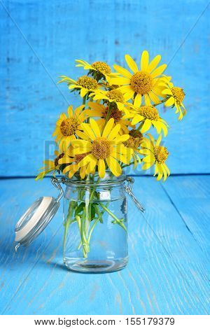 closeup of yellow daisies in a jar