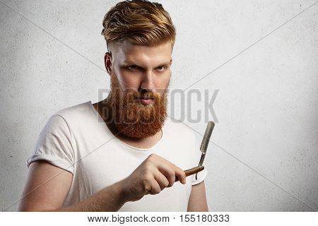 Redhead Hairdresser Or Barber With Fuzzy Beard Dressed In White T-shirt Demonstrating Sharp Blade Of