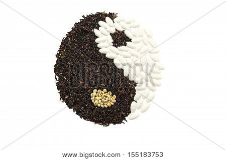 Black rice and white pill forming a yin yang symbol on brown wooden indicate blending of herb and medicine isolated on white background.Saved with clipping path.