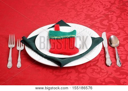 christmas place settings with stocking on red tablecloth