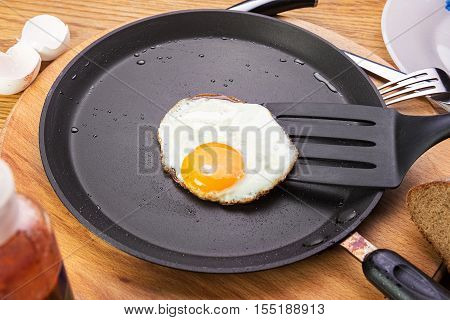 fried eggs on a pan. Pan stands on a wooden table around eggshells bread fork ketchup. view from above