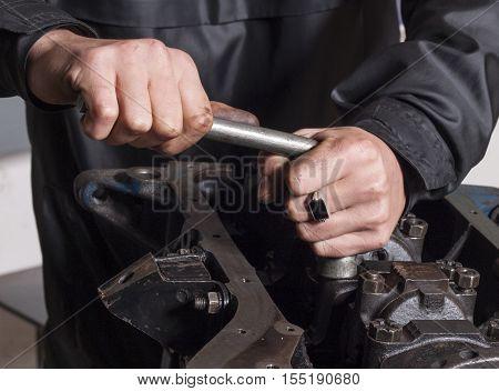 Car mechanic repairing an internal combustion engine