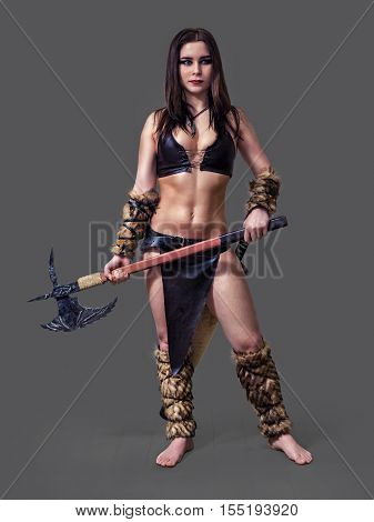 Beautiful athletic girl in the image of an ancient warrior barbarian with axe.