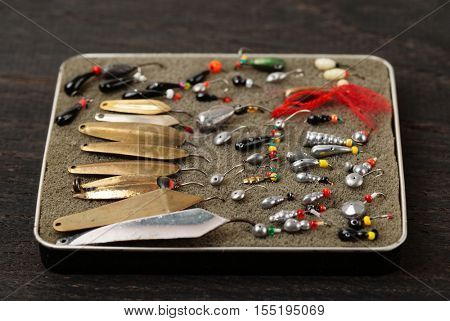 Set of lures for ice fishing on a wooden surface