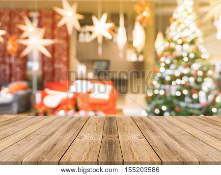 Wooden board empty table top on of blurred background. Perspective brown wood table over blur christmas tree and fireplace background can be used mock up for montage products display or design layout