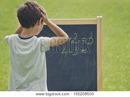 Boy thinking writing and counting on blackboard. Green outdoor background. School education concept.