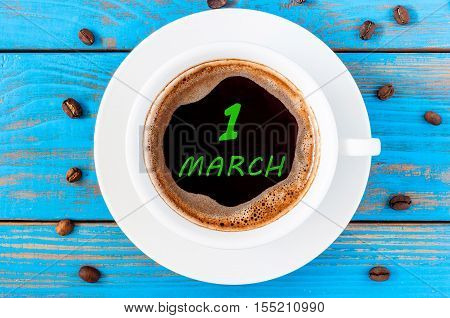 March 1st. Day 1 of month, calendar written on morning coffee cup at blue wooden background. Spring time, Top view.