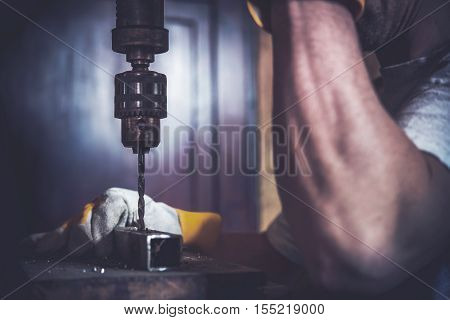 Metal Drilling Construction Work Concept Photo. Caucasian Worker and the Drill