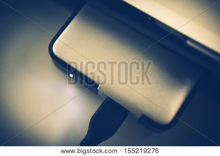 Small Portable Hard Drive Closeup Photo. Bluish Color Grading.