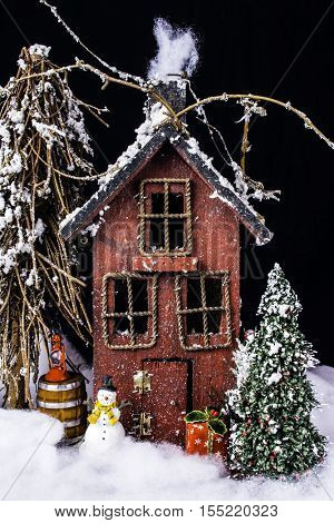 arts and crafts miniature scene of rustic house in deep snow with Christmas tree, snowman, and gifts