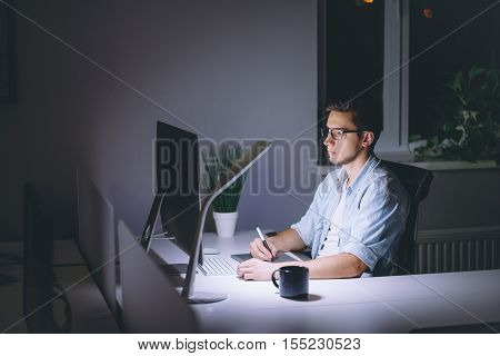 Young man working on computer at night in dark office. The designer works in the later time. A young man sits at the computer
