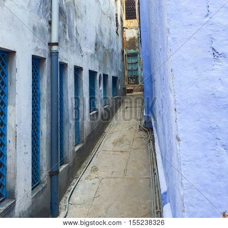 Narrow street of the old town. Ancient city tiny bystreet with blue painted houses. Colorful building of central India. Holy place Varanasi cityscape. Exotic travel photo with spectacular architecture