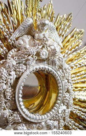 Vertical image in color of a metallic monstrance in close up with shallow depth of field