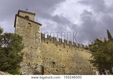 Castle wall in republic San Marino Italy. Tourists like to explore the medieval walls of ancient castle.
