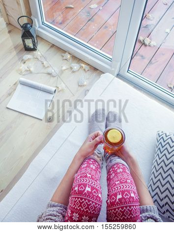 Close up view from above of woman's hands holding cup of tea with lemon. Wooden patio deck with fall leaves as the background