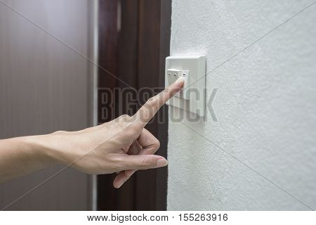 woman hand turning on light switch in the house