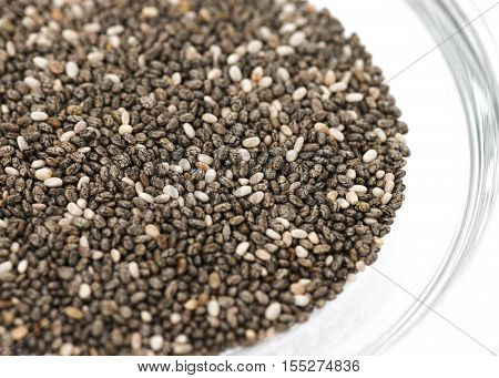 Selective focus of chia seeds in a glass bowl on a white background