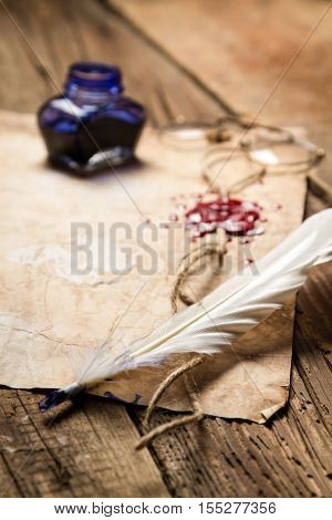 Closeup of a feather lying on old sheet of paper
