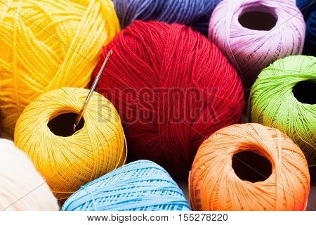Crochet and colorful knitting thread background. Bright background of balls of yarn variety with crochet on it. Handiwork, leisure, hobby concept