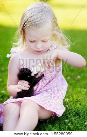 Adorable Little Girl Feeding Small Kitten With Kitten Milk From The Bottle