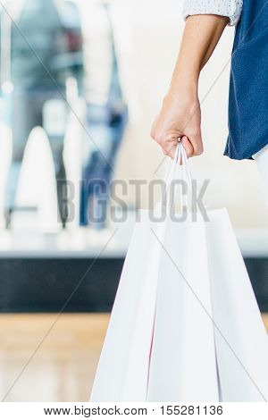 Black Friday. Close-up shot of hand with paper bags. Vertical indoors shot