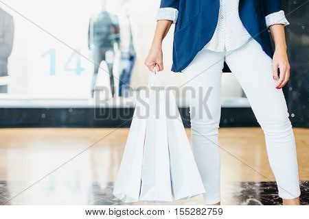 Black Friday. Shopping woman carrying goods she bought. Horizontal indoors shot