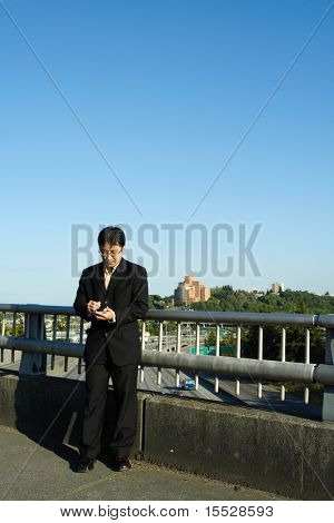 A businessman working on his PDA on a bridge