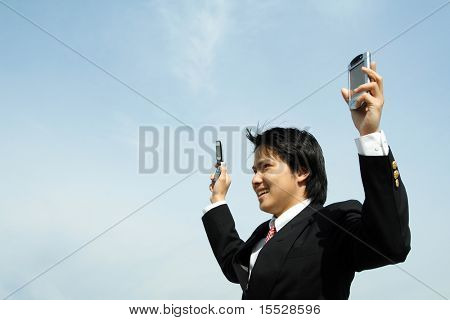 A businessman with arms up in the air holding a PDA and a cell phonee