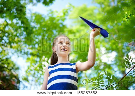Adorable Little Girl Playing With Blue Paper Plane Outdoors